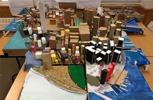 A scale model of lower Manhattan made out of cardboard and colored paper.