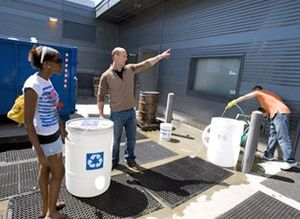 Teacher and student outside with water recycling bins