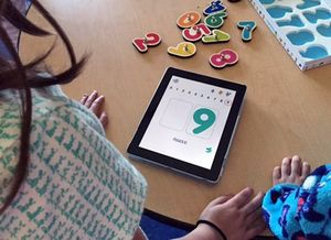 Two children at desk looking at numbers on a tablet