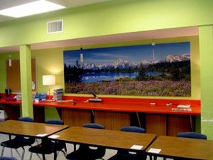 Classroom with green walls and a mountain and meadow mural on one wall