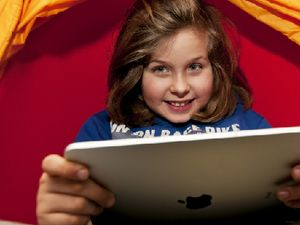 A young girl absorbed in her tablet
