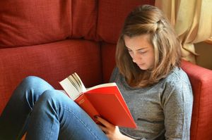 Teen reading a novel in a comfy chair