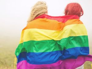 Two young adults wrapped in a rainbow flag