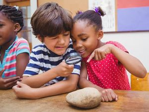 Two Students Playfully Examining a Rock