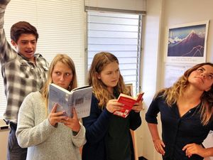 Four students standing together; two are reading while the other two are trying to distract them by striking funny poses