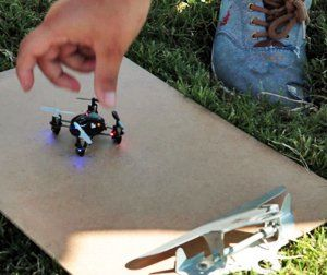 Close up of a kid's hand reaching for a small drone which is sitting on a clipboard on the grass