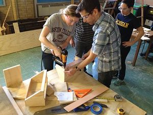 A photo of a teacher helping a student use the drill.