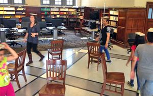Students playing musical chairs while balancing a book on their head