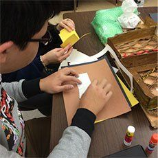 A photo of a student glueing pieces of colored paper together.