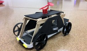 A vehicle created from a plastic tray, foam, and popsicle sticks