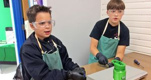 Two boys wearing safety goggles and green aprons