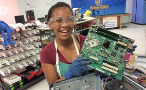 A girl wearing safety goggles, apron, and gloves, smiling holding up a computer circuit board