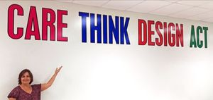 Woman standing in front of a wall under very large words: CARE THINK DESIGN ACT