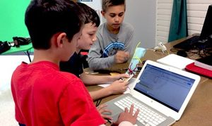 Three boys working together; one using an app on a laptop, two others working with pipe cleaners and paper
