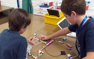 Two boys using LittleBits with batteries that light up pieces