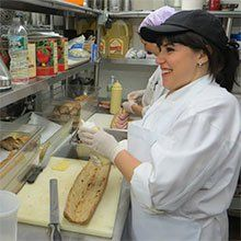 A photo of kitchen staff preparing large sandwiches.