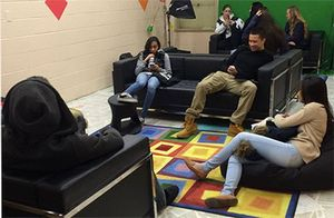 A photo of a group of high school students hanging out in the library's lounge area.