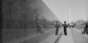 Black and white photo of a girl at the War Memorial with her hand touching one of the names