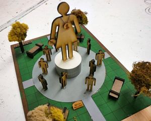 A model of a monument in a public square with grass and trees