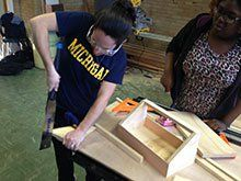 A photo of a girl sawing wood for her project.