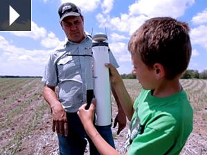 Cort and his father check a tool on their Nebraska farm.