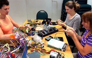 Three teachers sitting together at a table working with cords and circuits