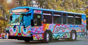 "An exterior shot of a tie-dye painted bus parked on the street with eyes painted on the front and ""Art"" painted on the side."