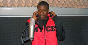 A teen male wearing headphones is standing next to and speaking into a microphone.