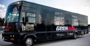 A close-up exterior shot of a large black-painted RV that says Geekbus in large lettering.