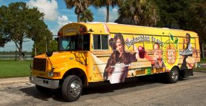 Nutrition is our mission is painted on a bus that's parked on the street. A picture of a teen girl with her arms raised in celebration, a young boy holding an apple, and a teen boy holding a sandwich are painted on the bus, as well.