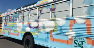 A close-up side exterior of a school bus painted blue with white clouds and purple, pink, green, yellow, and blue pipes.