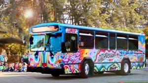 An exterior shot of a tie-dye-painted bus parked on the street