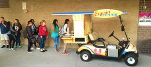 "Students are lined up behind a golf cart filled with food that says, ""Cruisin' Kitchen."""