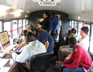 Teens and adults are sitting in a bus editing music on computers.