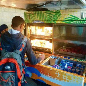 A student is reaching into the back of a golf cart filled with boxed milk, fruit cups, and wrapped hot foods.