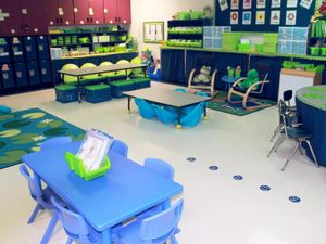 A classroom filled with different height tables and seating options, like rocking chairs and crate chairs.