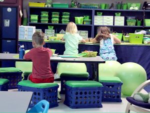 Students are sitting on yoga balls and crate chairs in a classroom.