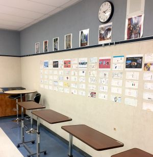 A line of standing desks against a classroom wall