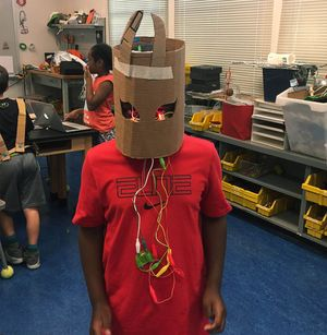 A student poses in a cardboard helmet.