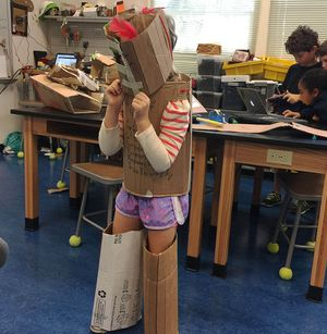 A girl poses in cardboard armor in a makerspace.
