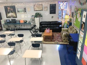 A classroom filled with desks, couches, and home furniture