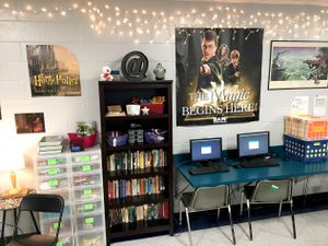 Bookshelves, storage bins, and a computer station against a classroom wall