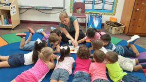 Audra Damron works on the floor with pre-K students.