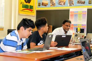 Troy Grant works with students.