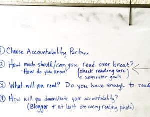 Reading accountability questions written on whiteboard
