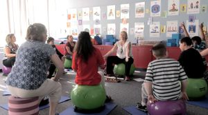 A group of students and adults sit on bouncing balls in a classroom.