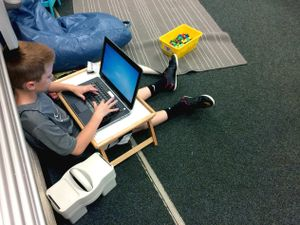 A young boy typing on a laptop on a lap desk while sitting on a classroom floor