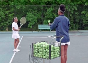 A teenage girl and younger girl are smiling, standing outside on a tennis court. The older girl is throwing a tennis ball to the younger girl.