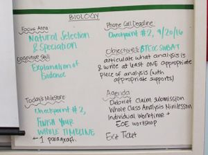 In a biology class, a whiteboard with the day's objectives, deadlines, milestones, area of focus, and cognitive skill focus outlined.