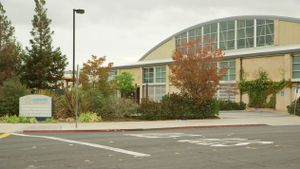 A street view of the exterior of Summit Preparatory Charter High School with a bush and tree garden in front of the school.